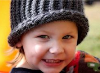 Happy, healthy smiling little girl wearing a knit hat.