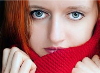 Close up picture of blue-eyed woman wearing a red knitted scarf.