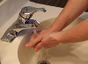 Person washing their hands over a sink with running water