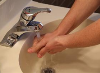 washing hands under running water in a sink.