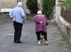 Two elderly people walking, the woman holding on to her back.