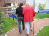 Person walking with elderly person.